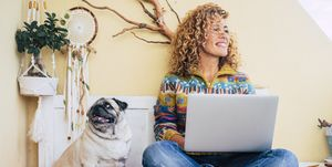 beautiful middle age lady curly hair work with a laptop outdoor at home in the terrace smiling and looking at his side. funny dog pug at her right sitting and looking. best friends forever and woman using technology concept