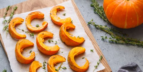 Baked pumpkin slices with thyme on a wooden board over grey table. Seasonal food vegetarian recipe.