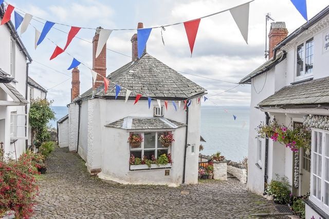 bunting and flowers adorn the cottages overlooking he sea at clovelly in devon