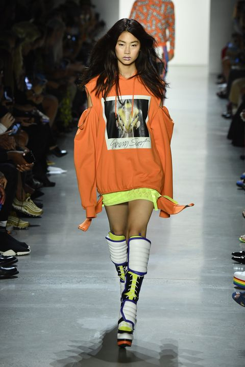 Fashion show, Fashion model, Runway, Fashion, Clothing, Shoulder, Orange, Yellow, Joint, Fashion design,