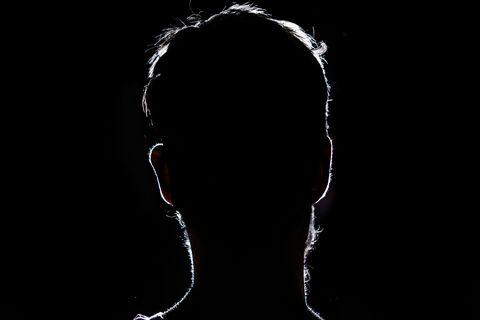 lighten portrait silhouette of a human head in the dark background
