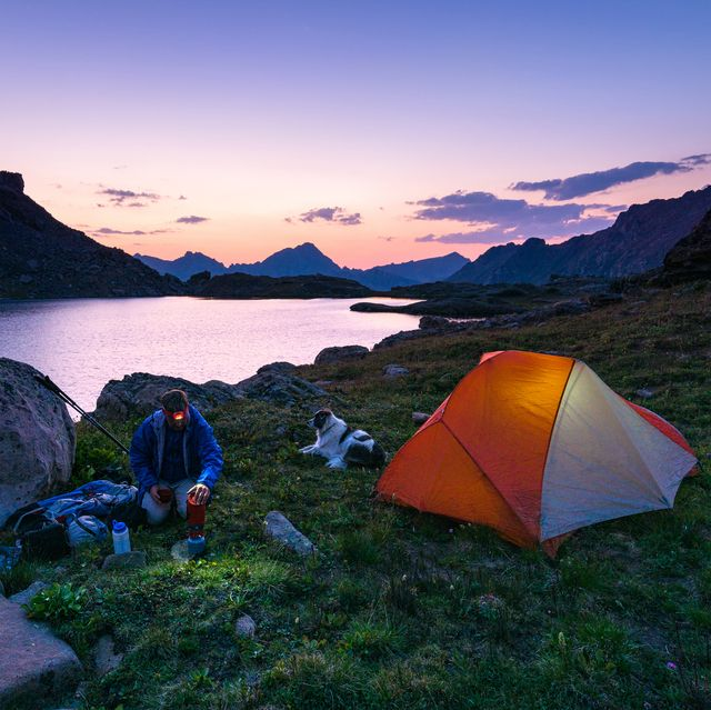 backcountry fly fishing camp at night with tent   scenic backpacker in beautiful alpine lake environment with glowing tent while boiling water for dinner