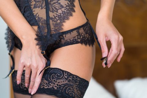 female hips in classical black stockings and garter belt in a bedroom interior