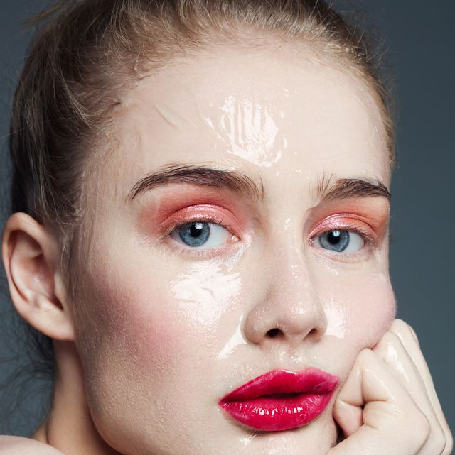 Beautiful woman with skin care product on her face