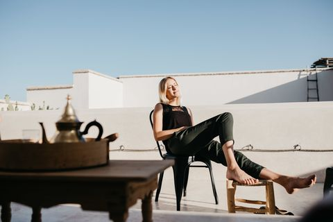 Smiling Young Woman Sitting On Chair At Building Terrace