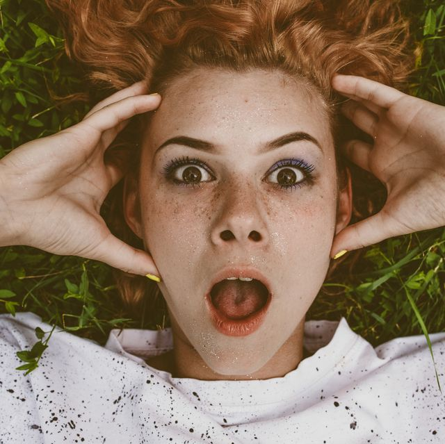 Close-Up Portrait Of Shocked Woman Lying On Field