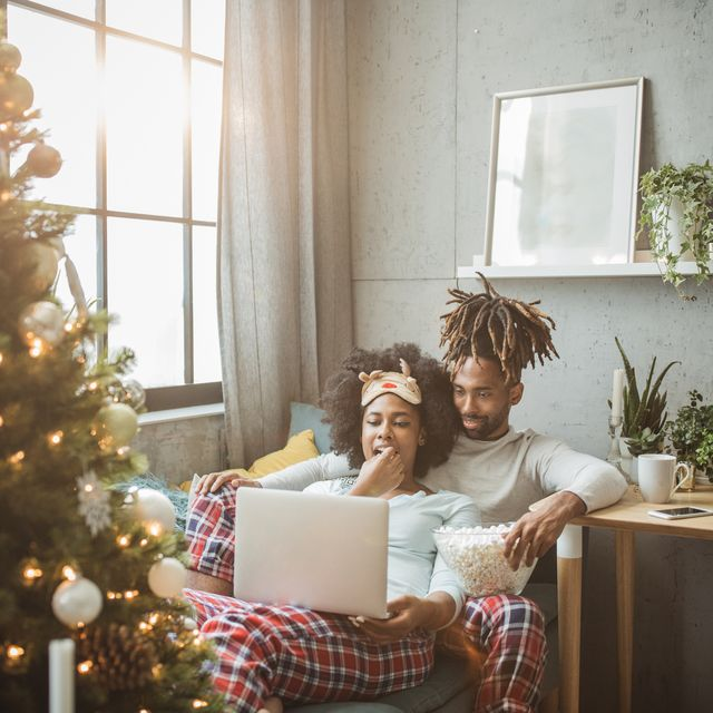 young couple celebrating christmas at home home is decorated with christmas ornaments and lights, they sitting on sofa and using laptop