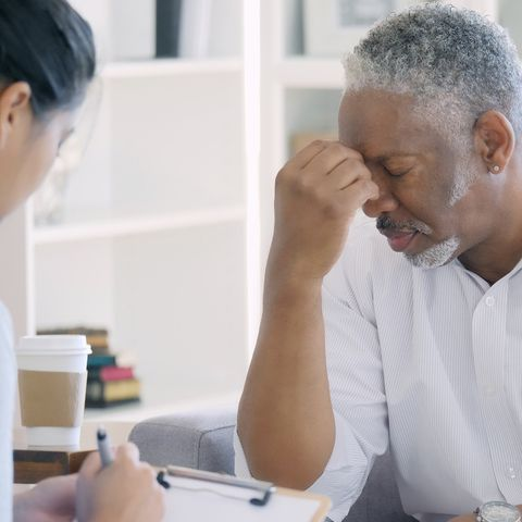 Distraught senior man meets with mental health professional