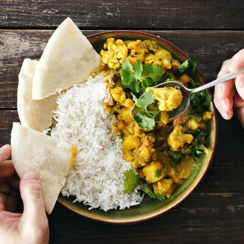 Man eats cauliflower spicy curry with rice and naan bread