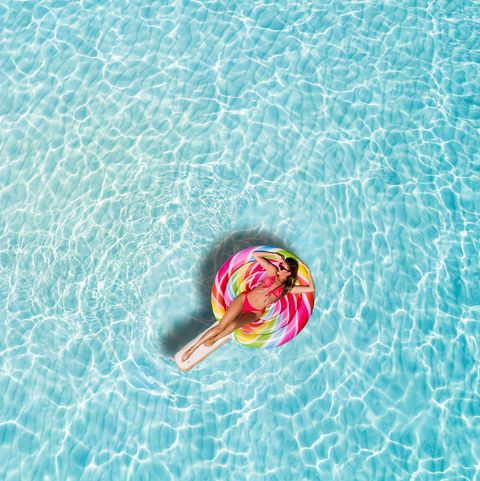 High Angle View Of Woman Lying On Inflatable Raft In Swimming Pool