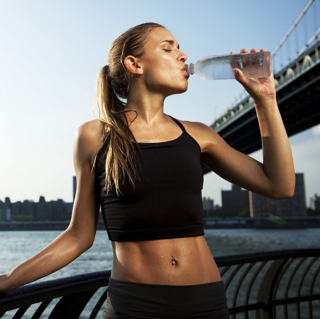 woman drinking water from a bottle after workout