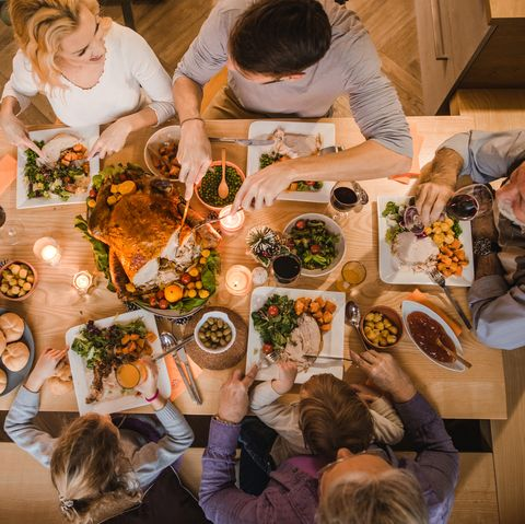 Above view of extended family talking at Thanksgiving dinner.