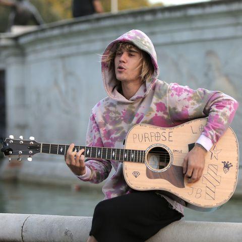 Guitarist, Guitar, String instrument, Musician, Street performance, Plucked string instruments, Musical instrument, String instrument, Pink, Acoustic guitar,