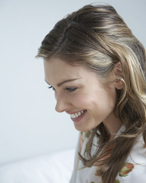 young woman smiling on bed,  close up