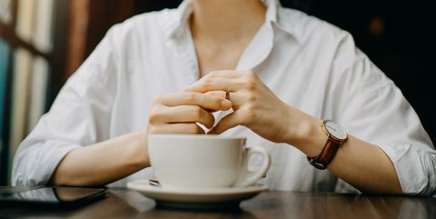 Woman touching the wedding ring on her finger nervously while having coffee and waiting in cafe