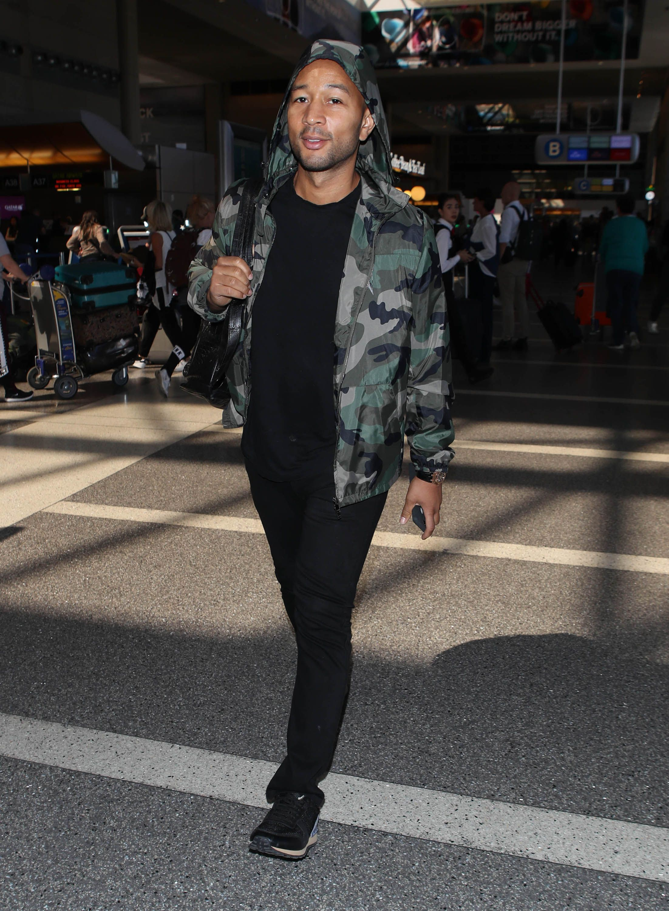 John Legend John Legend knows how to do just enough to make his style feel fresh but not overdone. A camo rain jacket and black suede runners are an easy example of how you can replicate it.