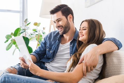 laughing young couple sitting on couch with digital tablet at home