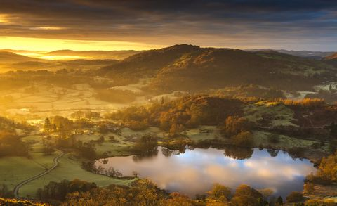 a stunning sunrise over the old loughrigg tarn at the heart of the english lake district national park, cumbria uk