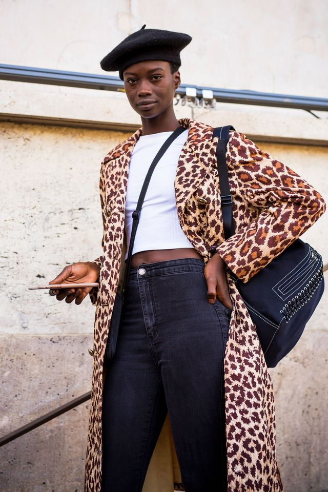 a model, wearing a white tshirt, black jeans, long leopard print coat, black backpack and black hat, is seen after the haider ackermann show on september 29, 2018 in paris, france