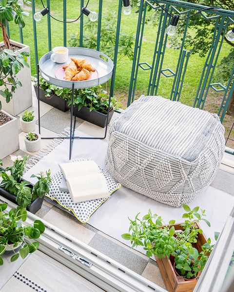 Vista de un puf blanco en un balcón con plantas y libro