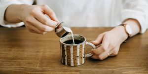 Close up shot of woman pouring milk in coffee cup and ready to enjoy it