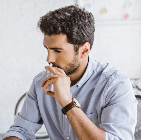 sick manager using nasal spray in office