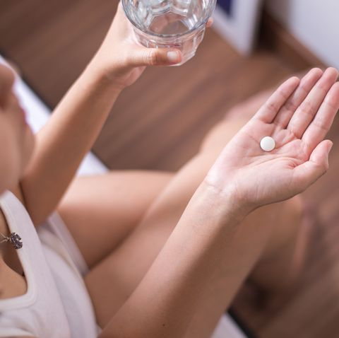 Woman with white pill painkiller on hand and a glass of water