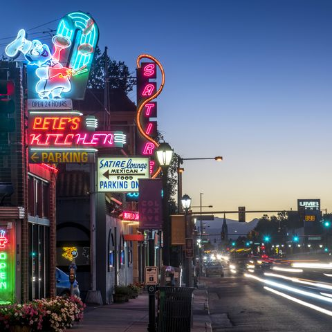 neon lights of vintage businesss on east colfax street in downtown denver, colorado