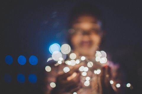 Defocused Image Of Woman With Illuminated String Lights At Home