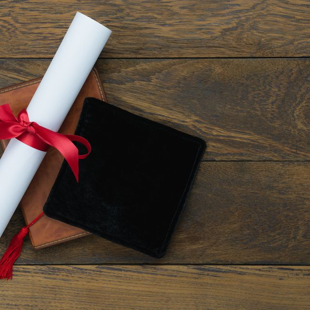 high angle view of degree with diary and mortarboard on table