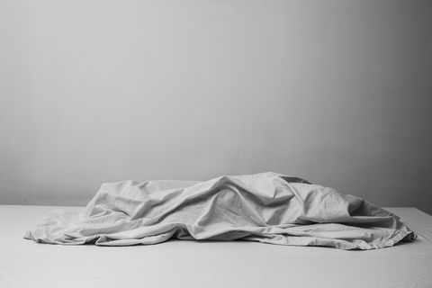 Crumpled Sheet On Bed Against Wall