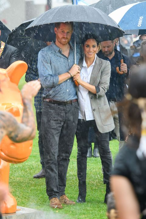 Umbrella, Rain, Fashion accessory, Interaction, Jeans, Event, Gesture, Denim,