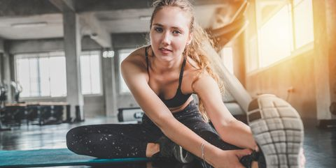 Portrait Of Young Woman Stretching Leg In Gym