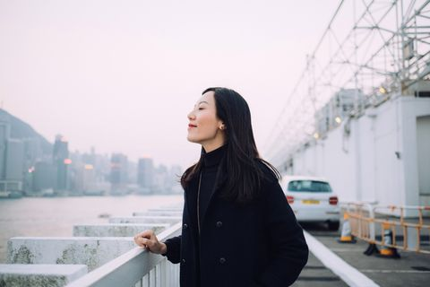 beautiful young woman enjoying the tranquility and gentle wind breeze with eyes closed by the harbour