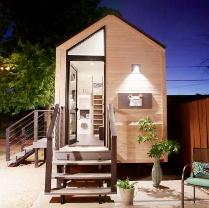 a tiny house with large glass windows, sits in the backyard at night, surrounded by trees and party lights