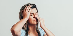 Woman holding her nose and head because sinus pain