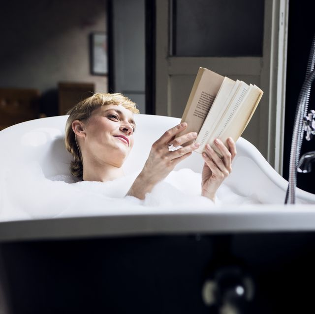 Portrait of relaxed woman taking bubble bath in a loft reading a book