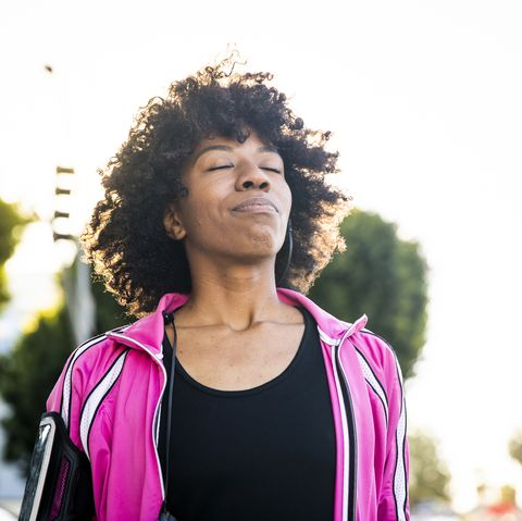 a young black woman adjusts her headphones during her workout