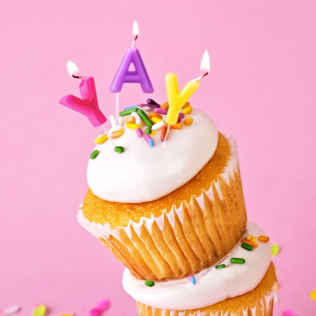 close up of a stack of yellow cupcakes with white frosting and sprinkles on a pink background top cupcake features letter shaped candles spelling out the word yay