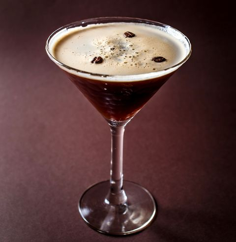 glass of espresso martini with coffee beans and vodka on elegant dark brown background
