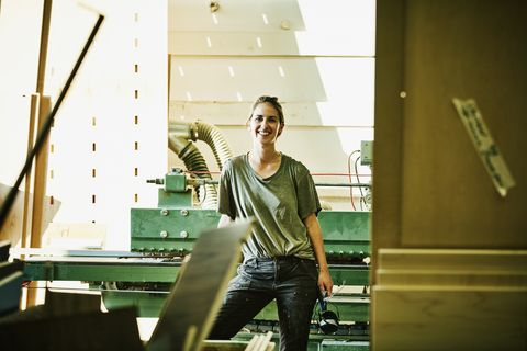 Portrait of smiling female woodworker in cabinet shop