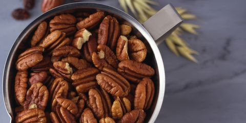 A container of pecans sitting on a counter with ingredients in the background.