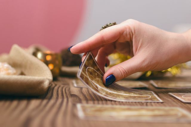 tarot cards and hands of fortune teller on wooden table background