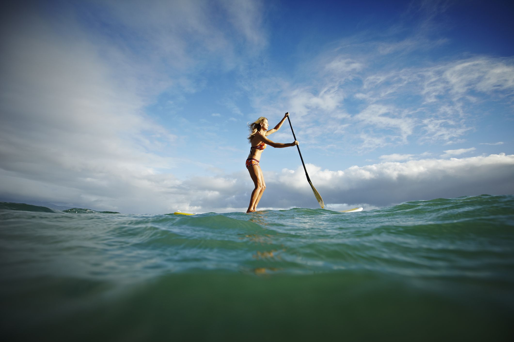 Female stand up paddle boarder paddling on ocean