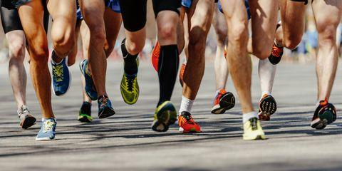 legs group men runners running on asphalt road