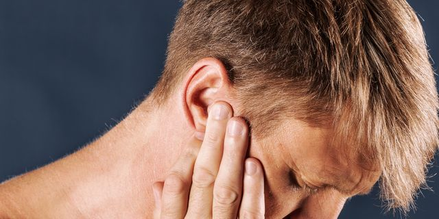man with fingers at ears looking like he's in pain