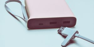 Power bank for charging smartphones and gadgets with a usb cable close-up on a green background. Modern technologies.