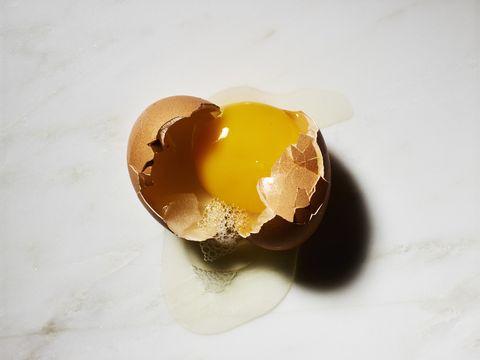 Broken egg in shell on white marble background
