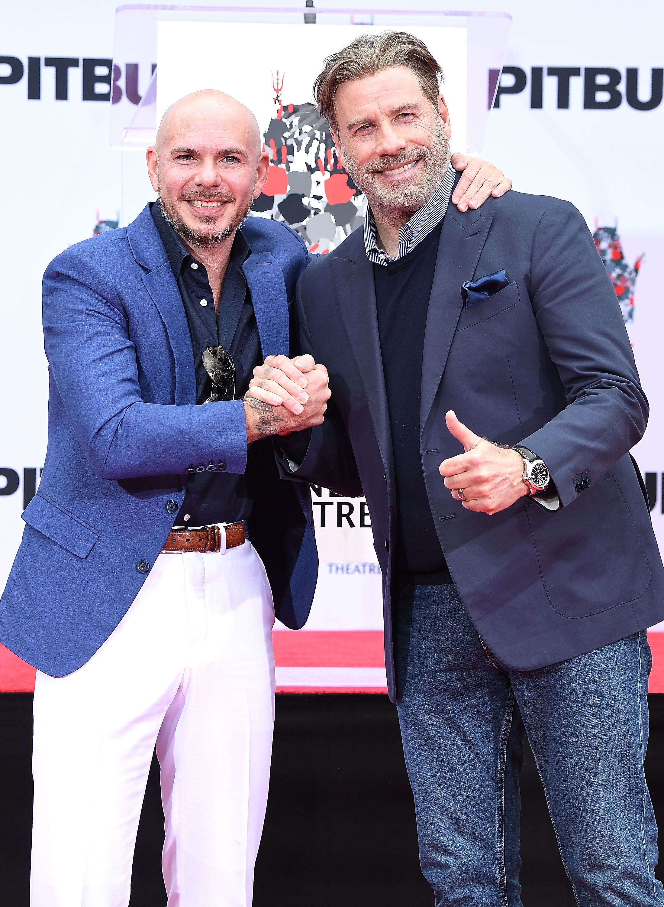 Pitbull and John Travolta at the TCL Chinese Theatre on December 14, 2018 in Hollywood, California.