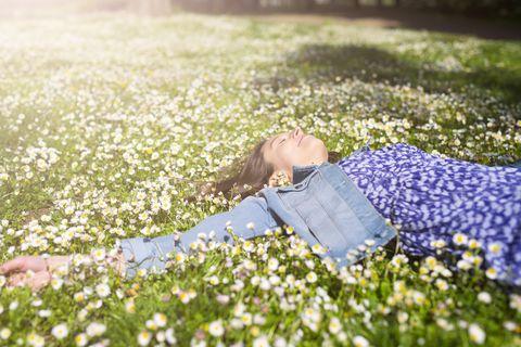 una chica tumbada feliz en un campo de flores ilustra un tema sobre rescue bach, la fórmula para volver a dormir bien